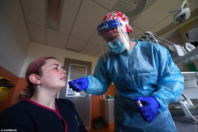 Nurse Carmen Kennett (right) conducts a COVID-19 test on healthcare worker Sarah Baker at a popup COVID-19 testing clinic at a dentist in Ballarat on August 14