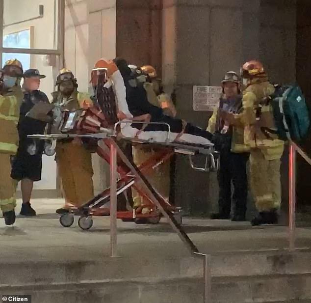 A person in uniform is pictured being carried away on a stretcher after the FDNY responded to a fire that had been started on the ninth floor of NYC's Manhattan Detention Complex