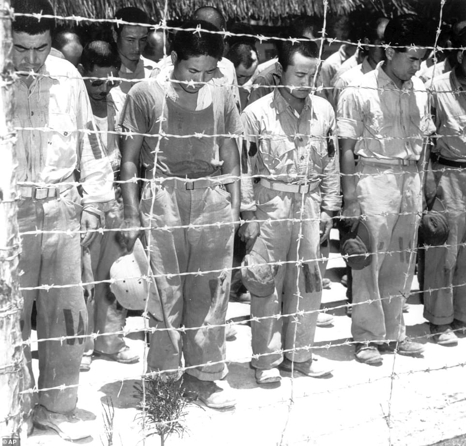 In this B/W file photo dated 15 August, 1945, Japanese prisoners of war at Guam, Mariana Islands, bow their heads as they hear Japanese Emperor Hirohito making the announcement of Japan's unconditional surrender