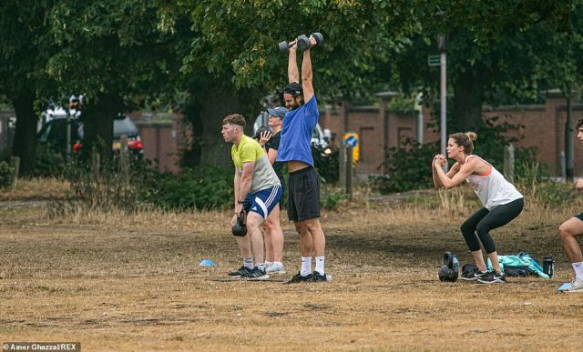 People worked out on the dried-out grass in Wimbledon Common as Saturday morning brought wet, overcast weather