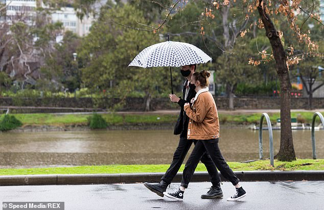 The lockdown has resulted in couples being forced to remain under the same roof despite the loss of love due to financial stress and stay at home directives (Pictured: a man and woman shelter under an umbrella in the rain in Melbourne)