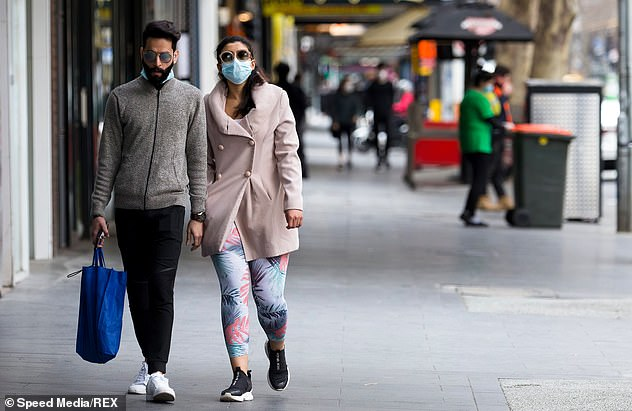 COVID-19 is putting increased pressure on relationships as couples battle financial pressure, job loss and mental health issue (Pictured: a couple walk hand in hand in Melbourne's CBD wearing face masks)