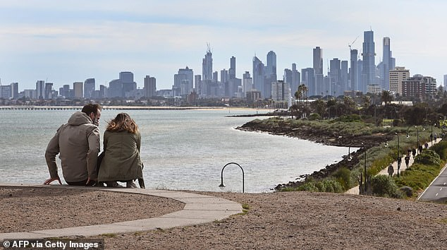 Relationship breakdowns are particularly dire for couples in the nation's coronavirus capital Victoria, (pictured a couple sit in front of the Melbourne skyline) who represent 40 per cent of this increase in inquiries for divorce