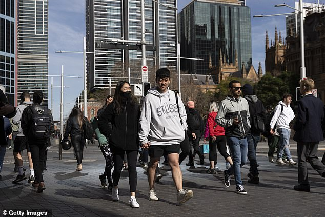 While COVID-19 has strengthened some relationships it has broken others (pictured: a pair hold hands as they walk through Sydney's CBD during the pandemic)
