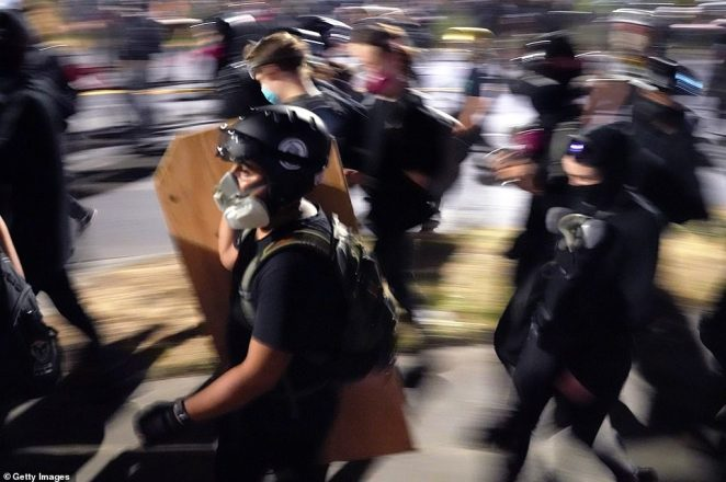 Protesters retreat up a residential street after police blocked the road, only to be faced with another line of cops in riot gear