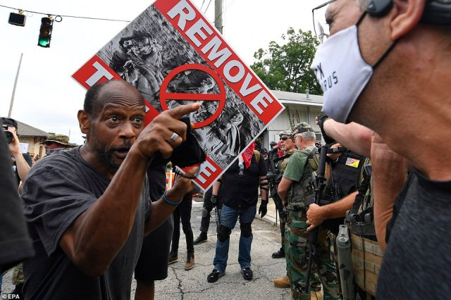 A counter demonstrator holding a placard calling for the removal of the Confederate monument is seen facing off with a member of an opposing group