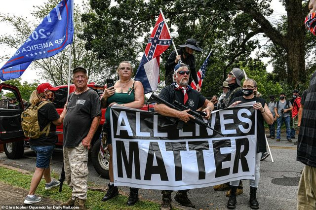 A man armed with a rifle holds up an 'All Lives Matter' banner while other far-right participants waved Confederate and Trump 2020 flags