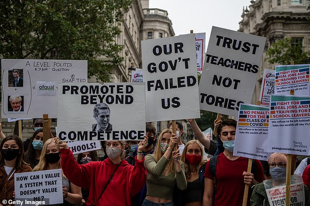 Students, teachers and parents hold placards and wear face masks as they protest against downgraded A level results due to Covid-19