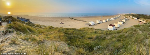 The sunset is pictured above on the dunes of Bleriot Beach, wheremigrants hide out before crossing the English Channel