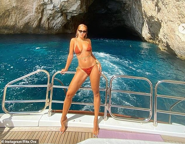 Legs for days: The beauty exuded confidence as as she put on a busty display in the tiny bikini top, which barely contained her cleavage as she posed