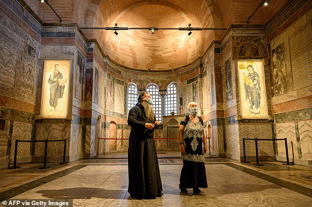 Pictured: A priest (L) and a woman visit Istanbul's Chora or Kariye Museum, formally the Church of the Holy Saviour, a medieval Byzantine Greek Orthodox church, on August 21, the day it was announced it would be converted into a place of Muslim worship
