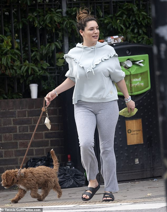 Figure-hugging: The former glamour model displayed her incredible figure in a pair of flared grey bottoms but she also kept things comfortable with her grey frilled hoodie