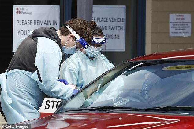 Medical staff perform COVID-19 test on patient at coronavirus testing center in Ballarat on Friday