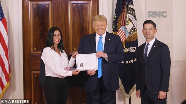 President Donald Trump holds a Naturalization Certificate while posing with a candidate for naturalization that was declared as U.S. citizen, during the largely virtual 2020 Republican National Convention broadcast from Washington, U.S. August 25, 2020