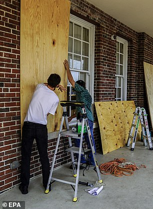Workers board up windows and doors of a hotel after a night of unrest in Kenosha, Wisconsin