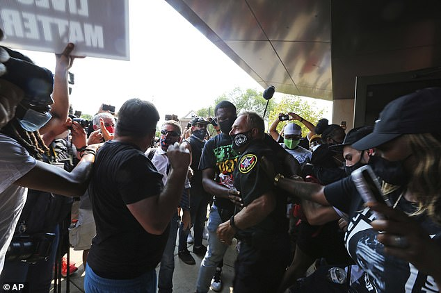 A Kenosha Police officer gets in the middle of protesters shoving each other who were trying to enter the Safety Building when they were denied access for a news conference on Monday