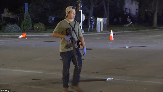 The man was seen walking the streets of Kenosha carrying a weapon, as 'self-styled militias' sought to fend off looters