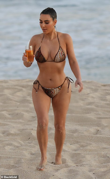 Sipping pretty: While back on the beach Kim she was given a chilly drink in a tall glass as a prop