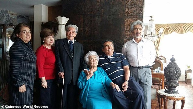 Pictured: Julio César Mora (third from left) andWaldramina Quintero (pictured sitting wearing the blue dress) with four of their five children