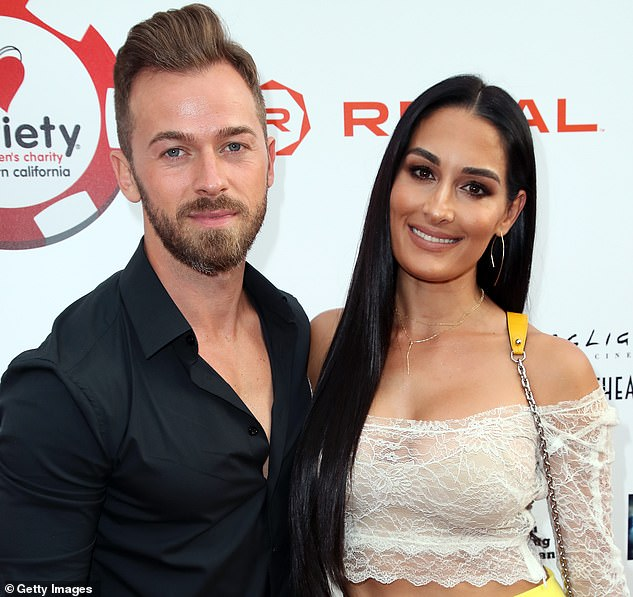 Engaged:Nikki and Artem started dating in January 2019 after being paired up on season 25 of Dancing With The Stars. They're pictured in July 2019