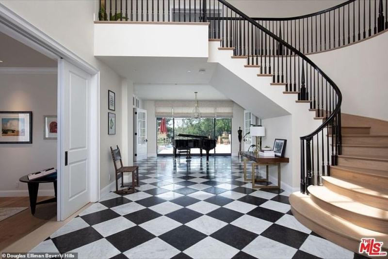 Stunning: Visitors to the mansion will be treated to elegant views of the foyer, with black and white checkerboard floors and a curving staircase leading up to the second floor