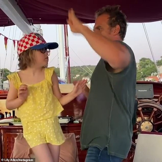 Elevated: Wearing a yellow playsuit and red-and-white baseball cap, Marnie stands elevated on a chair on the boat to meet the actor's height as she gets into the spirit of things