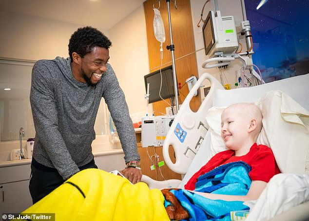 Having a blast: The photos in the post showed Boseman dressed casually in a charcoal hoodie and track pants as he as he spent some time with kids, all of whom looked delighted to see him
