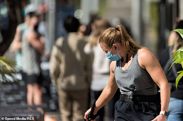 Melbourne residents ignored the warnings and took advantage of the sunshine over the weekend (a resident pictured walking her dog on Saturday)