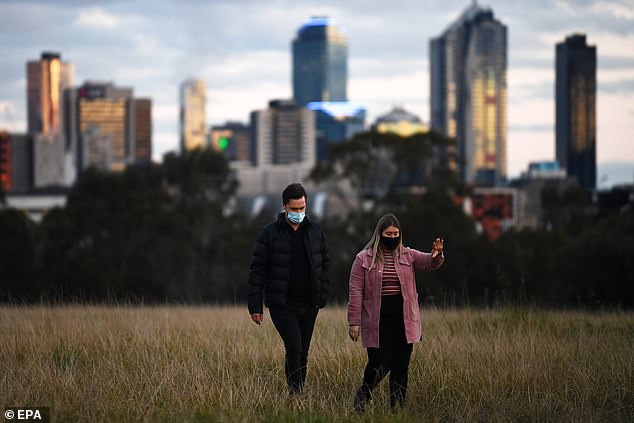 Victoriais currently on a hard lockdown, with Melburnians only allowed to leave their residences for food, exercise, work, caregiving and medical treatment. Pictured: People walking through a park in Melbourne during lockdown