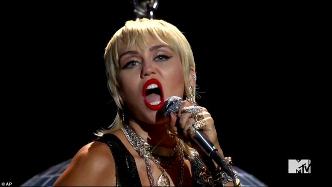 Wow: Showing off her long legs while holding on to a chain, Miley belted out her tune as she put on a spirited performance