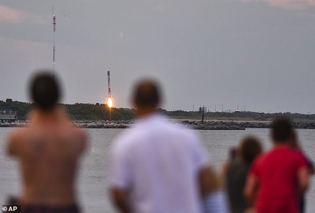 People at Cherie Down Park in Cape Canaveral, Florida watch the booster landing of the SpaceX Falcon 9, Sunday, Aug. 30, 2020