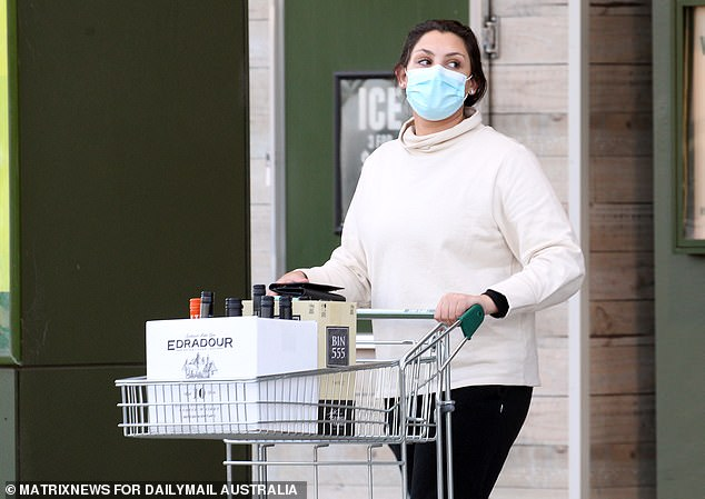 Alcohol and tobacco sales were up by 22 per cent in the week to August 23 when compared with an average week. Pictured: A woman in a face mask visits Dan Murphy's during Melbourne's coronavirus lockdown