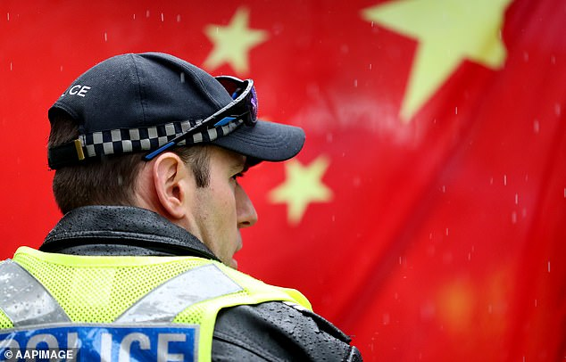 A police officer stands in front of a Chinese flag during a pro-democracy Hong Kong rally