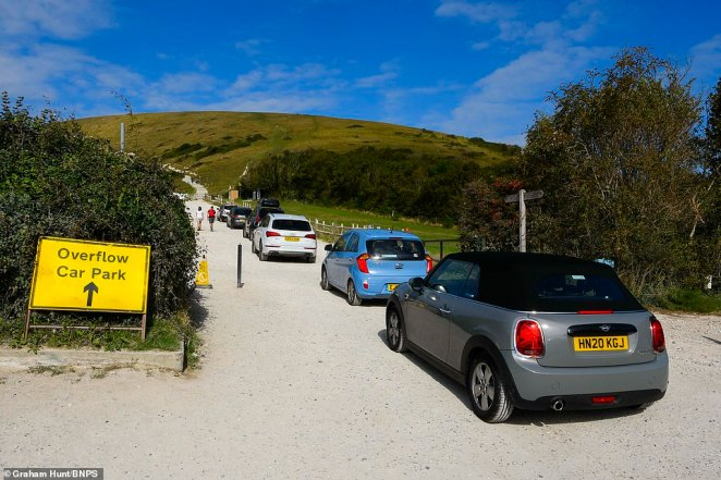 Despite the chill, the sun is still shining around the country which has encouraged some people to risk visiting the beach on their bank holiday. Pictured: Cars queue to enter the car park at Lulworth Cove in Dorset this morning