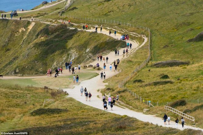 A few brave souls determined to make the most of their chilly bank holiday walk along the coastal path to Durdle Door in Dorset this morning