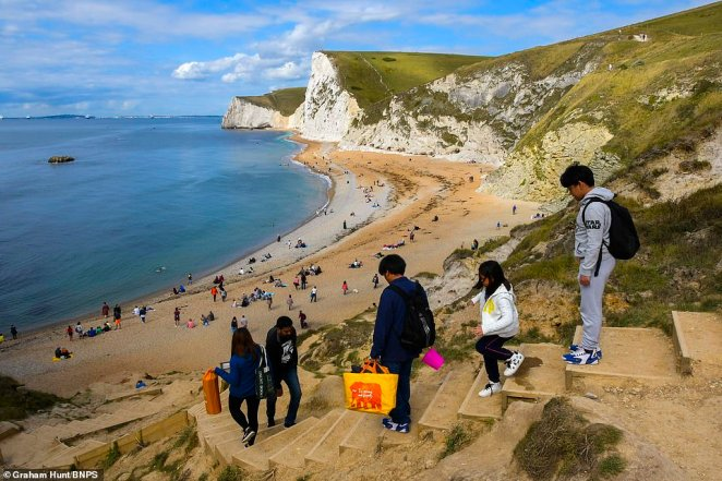 The chilly weather hasn't deterred some people from making the most of their bank holiday break as a few brave souls have travelled to the beach. Pictured: Holidaymakers descend the steps to Durdle Door beach in Dorset today