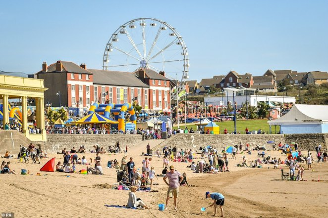 The sun shines gloriously at the beach on Barry Island, Wales, as people enjoy their bank holiday break in temperatures well below the average for this time of year
