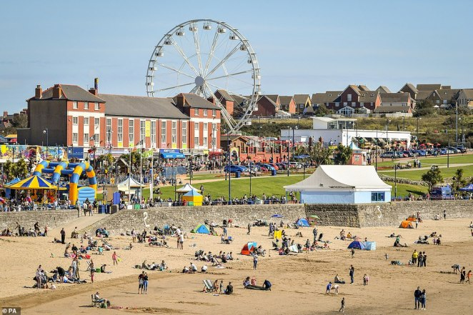 Despite temperatures falling to as low as 11C in some areas of the country, people have still made the trip to beaches such as at Barry Island (pictured today)