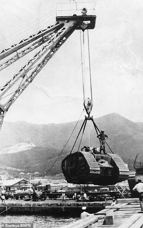 A tank is lifted by a crane while an officer stands on top