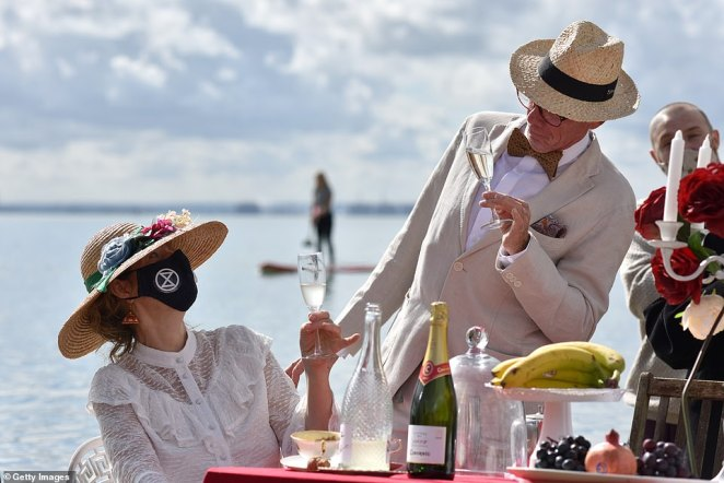 Climate activists wearing early 20th Century dress waded into the water off Chalkwell Beach, Southend-on-Sea, to quaff Champagne and sip tea around a semi-submerged dining table