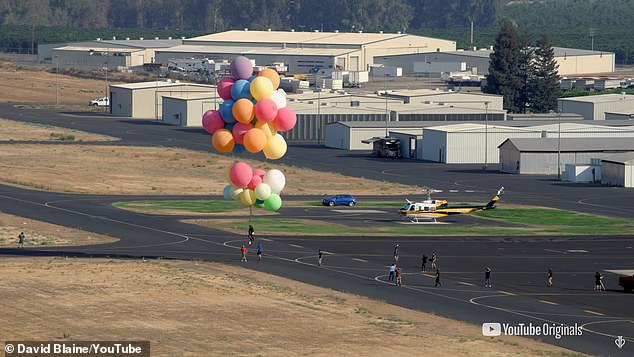Practice makes perfect: Blaine pictured rehearsing the stunt holding on to the weather balloons