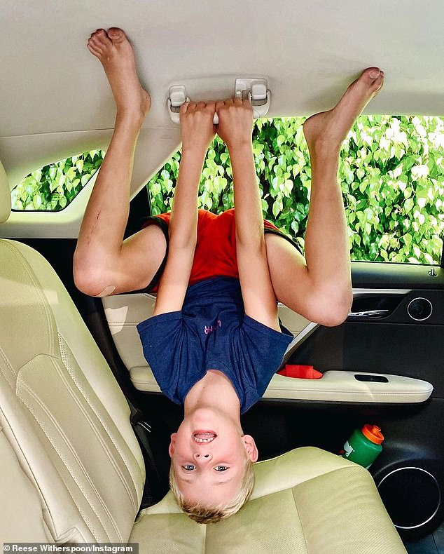Acrobat:The final photo showed Tennessee impressively clinging upside down to the roof handle of his family's luxury SUV
