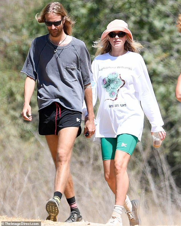Keeping cool: The stunning couple were seen sporting laidback hiking looks as they strolled casually with coffee in hand while they kept their masks close