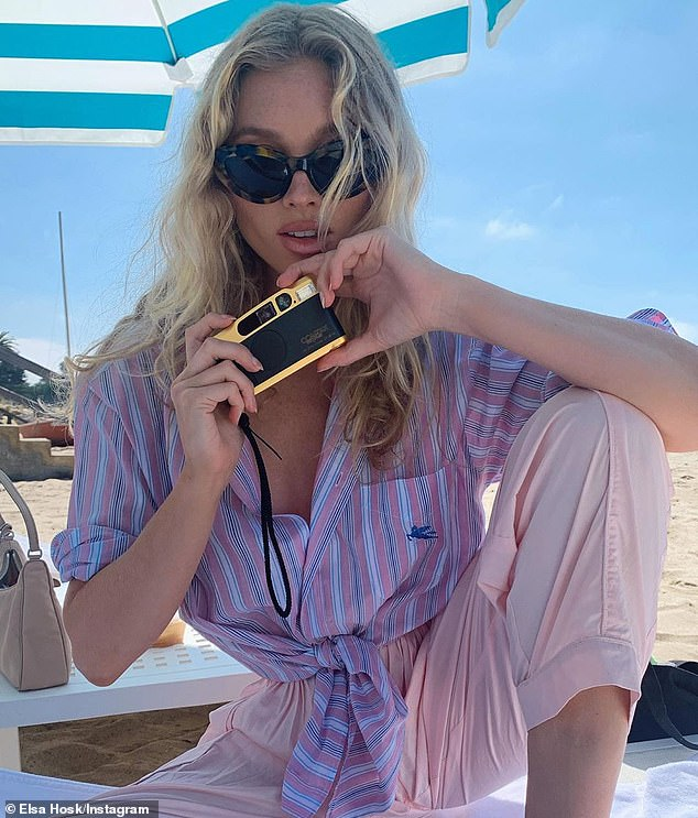 Tickled pink: Elsa who clearly has taken up a love of photography recently poses by the beach in a beachy pink ensemble as she holds her film camera in hand