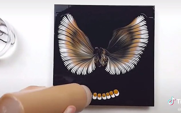 She used beads to spread splodges of brown and white paint across a black background. Once finished, she had depicted two stunning wings