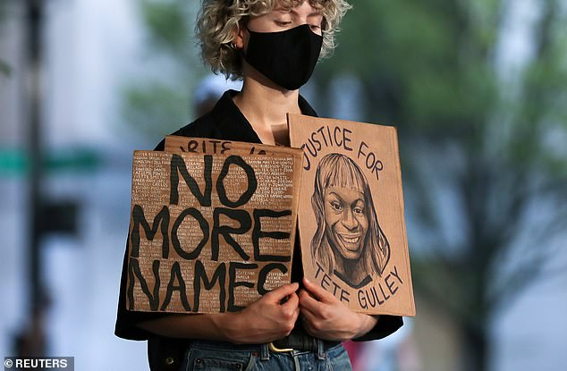 A protester holds up a sign during a 'meditation walk' in support of Black Lives Matter through downtown Portland on Tuesday