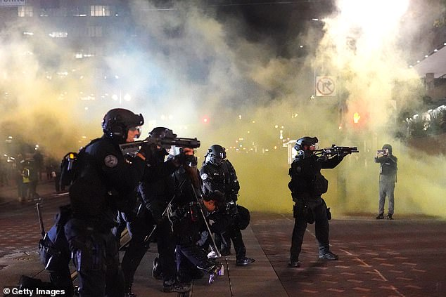 Portland police officers fires less lethal rounds through smoke while dispersing a crowd of about 150 people from Portland City Hall on August 25, 2020 in Portland, Oregon