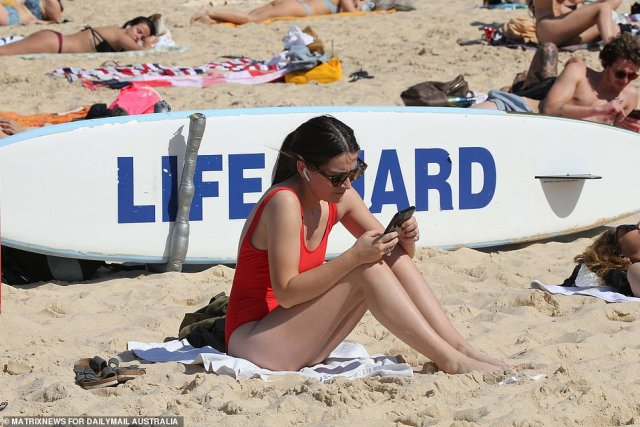A woman in red messages on her phone as she soaks up the sun on Thursday. Temperatures reached a scorching 29C