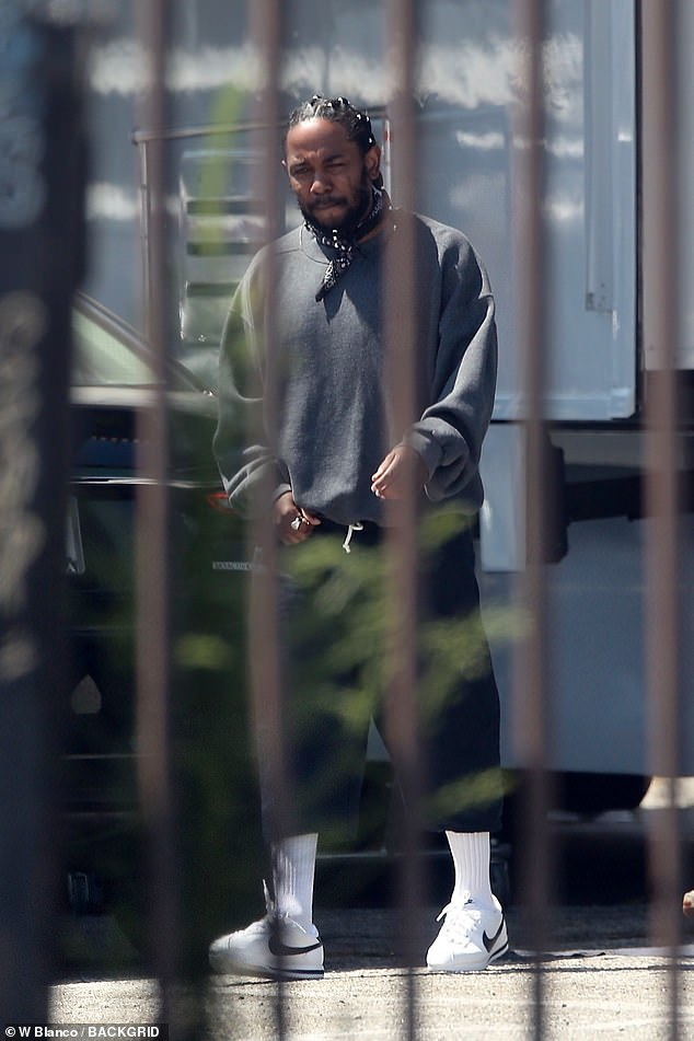 Kendrick's look:He was later seen wearing a grey sweatshirt with a black bandanna tired around his neck, along with black shorts, white socks and white Nike Cortez sneakers