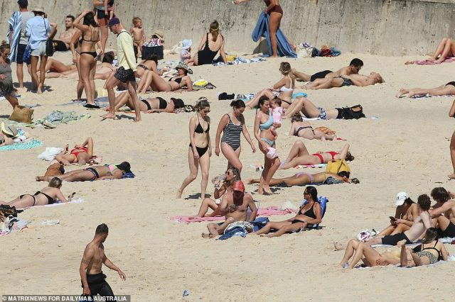 Sunbathers lay metres apart at Coogee Beach on Thursday, ensuring they social distance due to the COVID-19 threat